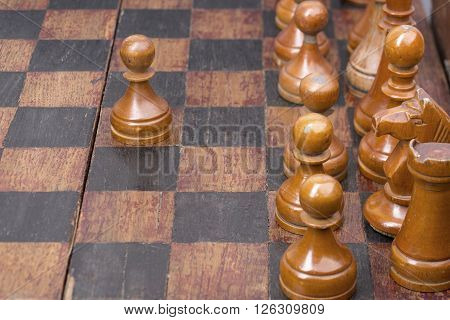 row of vintage wooden pawns on chessboard with focus on second piece