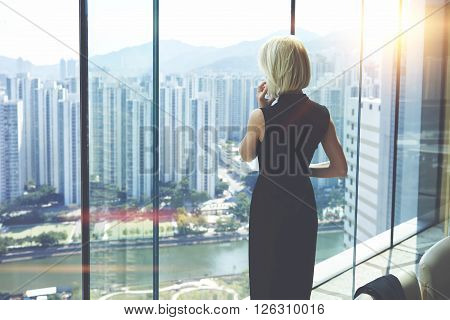 Back view of young entrepreneur is calling via cell telephone while is standing in her private office against window with view of developed business district with high skyscrapers.Copy space for text