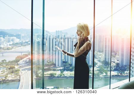 Young proud businesswoman is talking on her mobile phone with client and reading order on digital tablet while is standing near office window with view of developed business district in China