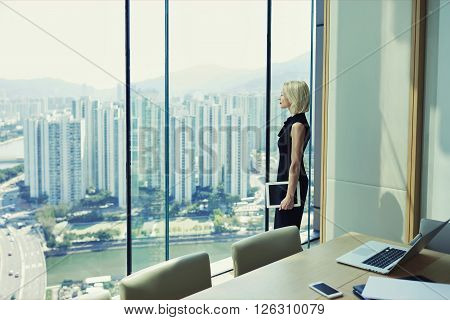 Blonde woman proud CEO is holding touch pad and looking in office window with cityscape while is standing in conference room near table with open laptop computer during her business trip in Hong Kong