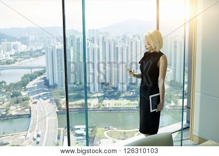 Confident fyoung emale financier with touch pad in hand is reading financial news in network via mobile phonewhile is standing near private office window with view of high buildings business district
