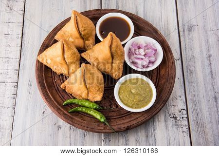 samosa snack with imli chutney or tamarind sauce, onion and green fried chili, served in wooden plate