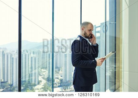 Young man serious managing director is calling to his manager to find out why he had not sent to e-mail on digital tablet reporting on implementation of work while is standing near office window