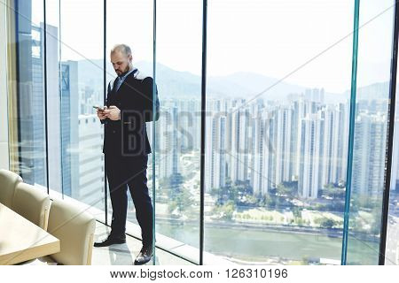 Confident managing director is typing text message on cell telephone while is waiting beginning of the conference with staff while is standing near window with copy space background for your content