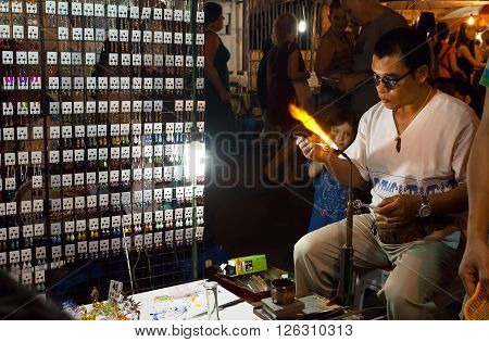 CHIANG MAI, THAILAND - FEB 20: Glassblower making new glass products for sale during night market with local shops and masters on February 20, 2016. Population of Lampang is near 59000 people