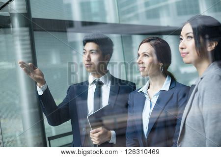 Group of business people looking though window
