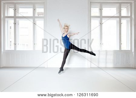 Young dancer practicing in studio. Motion blur.