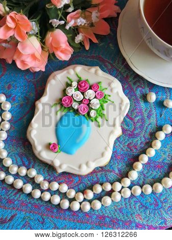 Gingerbread schedule glaze and decorated with edible flowers is on the table with a cup of tea, flowers and white pearls