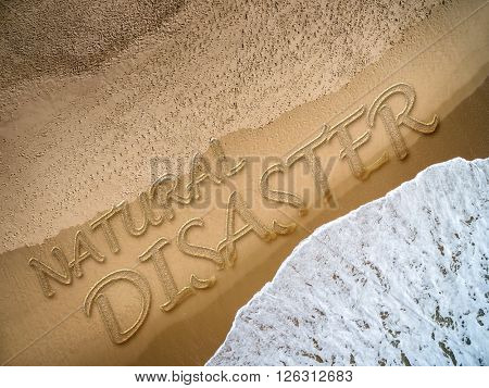 Natural Disaster written on the beach