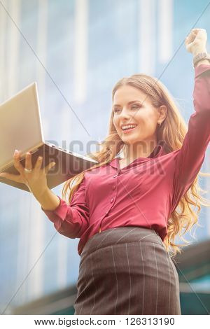 Businesswoman celebrating victory with her partners while speaking with them over Skype. Laughing lady raised left hand. She is happy.