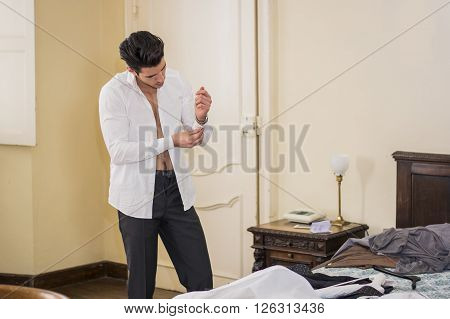 Handsome young man putting on white shirt while buttoning up sleeve in bedroom