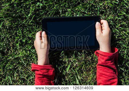 Hand holding tablet pc over green grass background