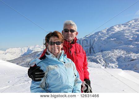 Retrato de un hombre mayor y una mujer senior sonriendo en paisaje nevado