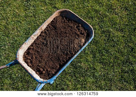 gardening trolley full of soil on green grass background