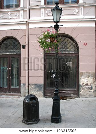 Street of the old city black lantern decorated with flowers and an urn