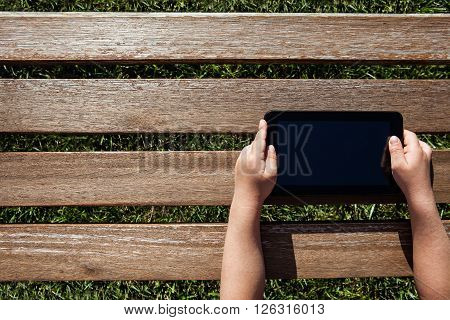 Hand holding tablet pc over wooden background