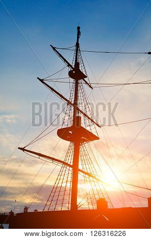 Picturesque travel background - closeup vertical view of masts and rigging of sailing ship on the background of the dramatic sunset sky.