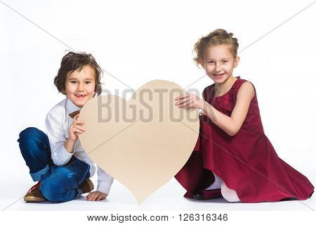 Boy and girl holding a cardboard heart. Love concept.
