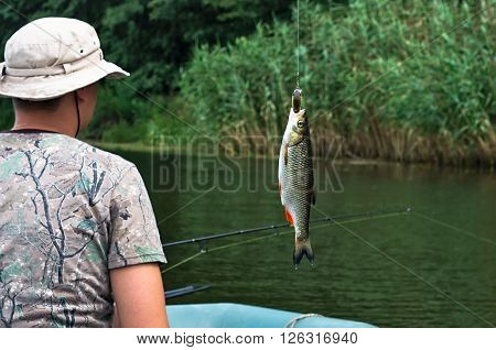 fisherman and fish chub on the background of the river