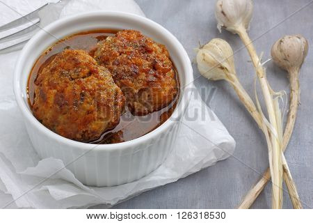Ramekin filled by meatballs and spicy broth on paper cloth