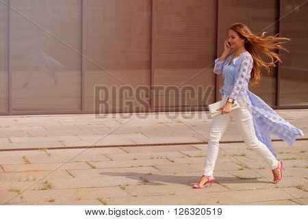 Businesswoman with long brown hair speaking over smart phone and hurrying up. Lady with blue coat on walking along the office building. Toned image.