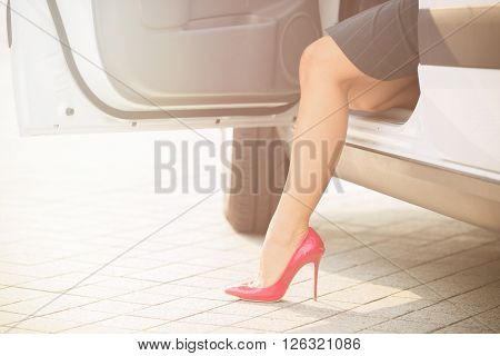 Business woman sitting in her car. She is going to get out from the car. Slim and slender woman's leg on high heels looking from the car. Toned image.
