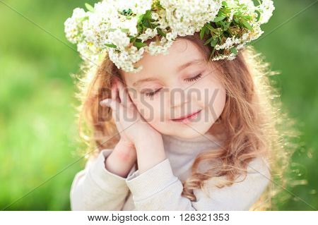 Cute baby girl 3-4 year old wearing flower wreath over green nature background. Posing outdoors. Childhood. Spring season.