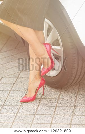 Close-up picture of woman's legs near car's wheel. Pretty lady on pink high heels in grey skirt posing for photographer. Toned image.