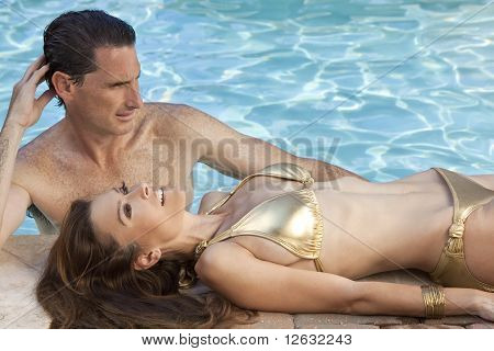 Beautiful Couple Relaxing By Swimming Pool