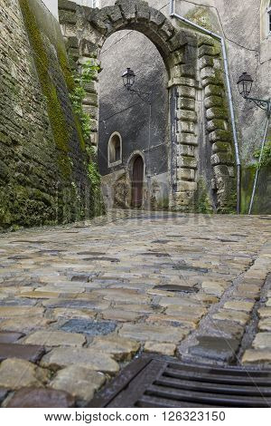 It is the old archway on the cobbled road.