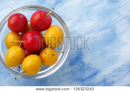 Glass bowl filled by yellow and red mirabelle plums over blue painted textile background. Copy space. Overhead view.