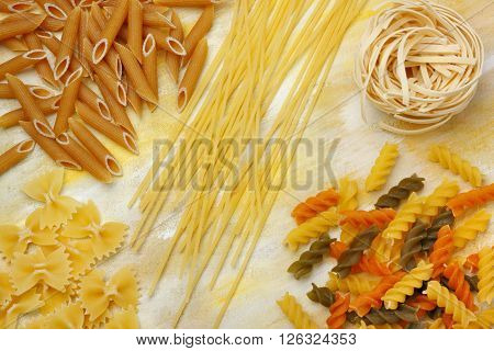 Variety of dry raw pastas over painted textile background. Overhead view.