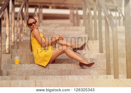 Fashion girl sitting on stair of office building with orange cocktail. Smiling lady in sunglasses enjoying her time after hard day. Toned image.