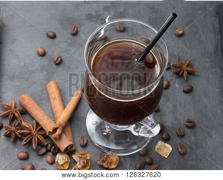 Black coffee in a glass on a black board with cinnamon sticks spices coffee beans anise stars sugar and caramel. Hot drink - frappe latte cappuccino. Top view a cup of coffee.