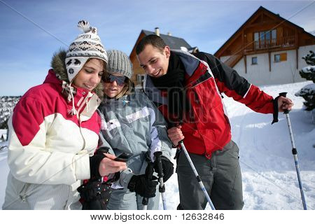 Young woman watching her mobile phone near friends in snow
