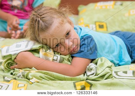 Little Girl Sitting On A Double Bed And Frightened Looks Into The Distance