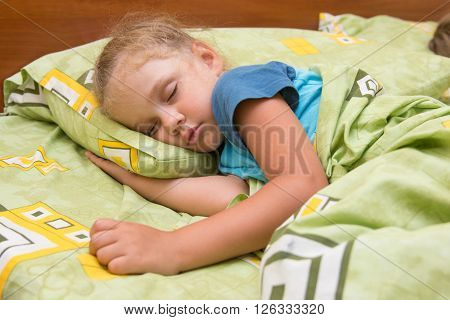 Little Girl Sleeping On Her Side In Bed With His Hand Under The Pillow And Covered With A Blanket