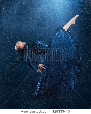 The young beautiful modern dancer in long dress dancing under water drops in blue aqua studio