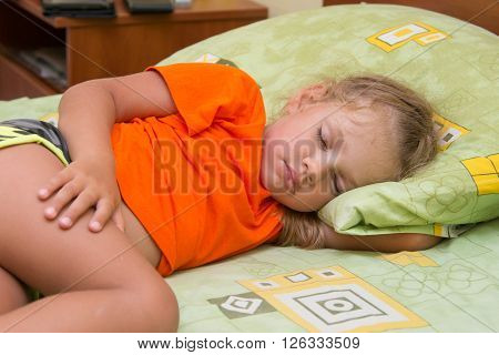 Little Girl Sleeps On His Side In His Hand Under The Pillow Of The Bed