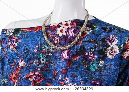 Floral top and silver necklace. Female mannequin wearing bijouterie necklace. New accessory for young girls. Merchandise at low price.