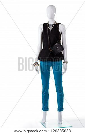 Dark top and folded pants. Trousers with purse on mannequin. Woman's fashionable outfit and bag. Black v-neck top in stock.