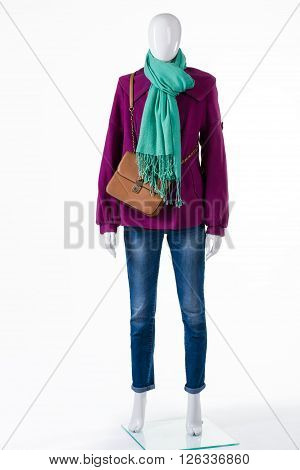Purple coat with brown bag. Coat and purse on mannequin. Female autumn outfit on display. Colorful apparel with leather handbag.