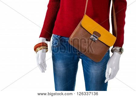 Red sweater with colorful accessories. Mannequin wearing pullover and bijouterie. New leather bag with bracelets. Lady's light accessories on showcase.