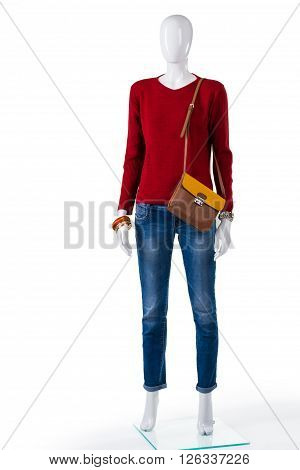 Skinny jeans and red sweater. Mannequin wearing pullover with jeans. Idea for woman's autumn outfit. Trendy clothing in local boutique.