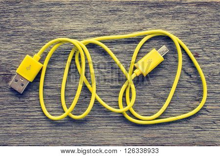 Yellow USB cable on wooden table - top view
