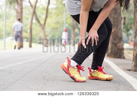 Sports injury. Cramp. Woman holding sore leg muscle while jogging in park