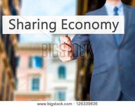 Sharing Economy - Businessman Hand Holding Sign