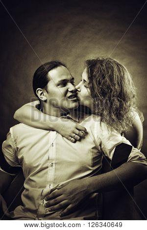 Redhead girl kissing her boyfriend over dark background