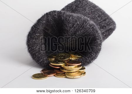 euro coins in a wool sock on white background