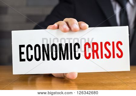 Economic crisis message on white card and hold by businessman